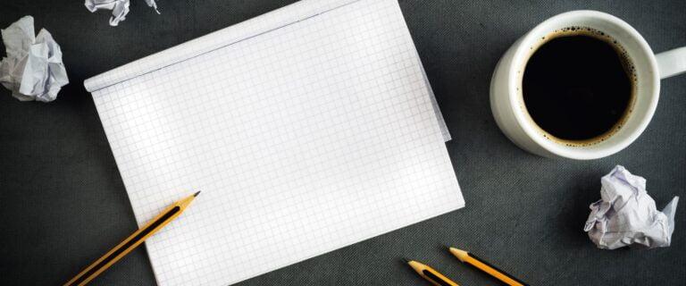 Σημειωματάριο για να σημειώσεις τους στόχους, μολύβια και μια κούπα με καφέ